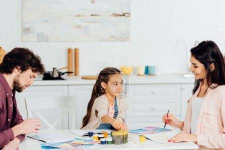 Photo pour Gosse mignon regardant la mère tandis que le dessin de père sur le papier - image libre de droit