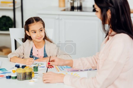 Photo pour Foyer sélectif de l'enfant heureux regardant la mère retenant le pinceau - image libre de droit