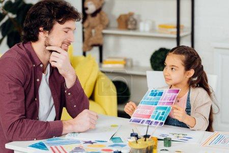Photo pour Papier de fixation mignon d'enfant avec des rayures colorées près du père heureux - image libre de droit