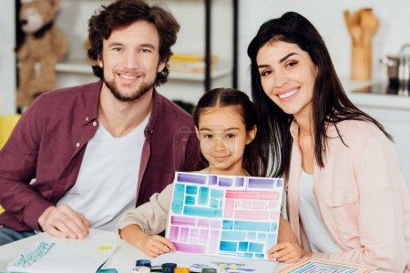 Photo pour Le papier de fixation gai d'enfant avec des rayures colorées près du père et de la mère heureux - image libre de droit