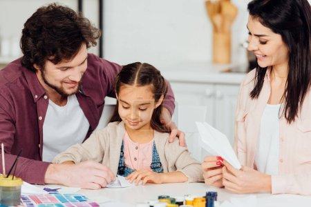 Photo pour Père heureux près de la fille mignonne avec l'avion de papier à la maison - image libre de droit