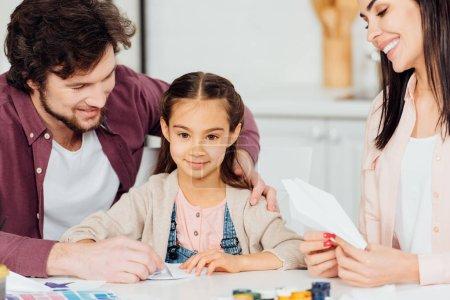 Photo pour Père heureux souriant près de la fille mignonne avec l'avion de papier à la maison - image libre de droit