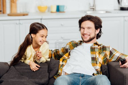 Photo for Happy kid smiling near cheerful father sitting on sofa - Royalty Free Image