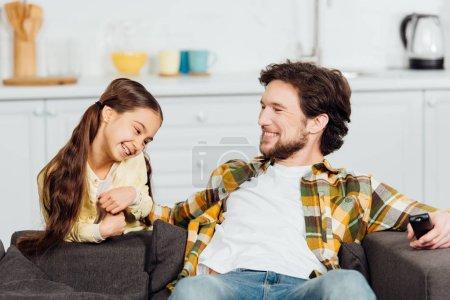 Photo pour Père gai s'asseyant sur le sofa et retenant le contrôleur à distance près de la fille de sourire - image libre de droit