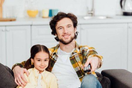 Photo pour Foyer sélectif du père heureux s'asseyant avec la fille mignonne sur le sofa et retenant le contrôleur à distance - image libre de droit