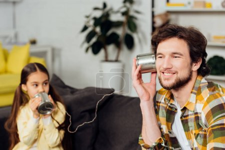 Photo for Selective focus of cheerful father holding can phone while kid talking at home - Royalty Free Image
