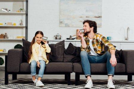 Photo pour Heureux fille tenant peut téléphone et joyeux père parler et assis sur le canapé - image libre de droit