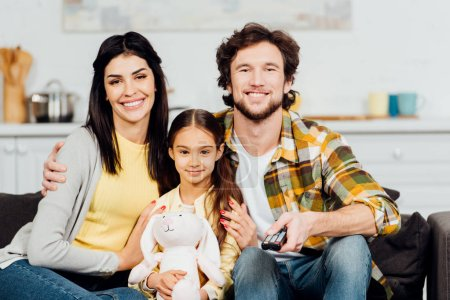 Photo for Cheerful kid holding soft toy and sitting near happy parents at home - Royalty Free Image