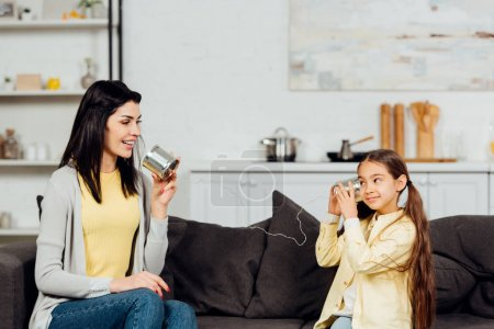 Photo for Cheerful mother talking while holding tin can and playing with happy daughter - Royalty Free Image