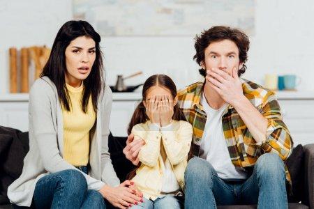 Photo pour Choqué mari et femme regardant la télévision près de la fille couvrant le visage - image libre de droit