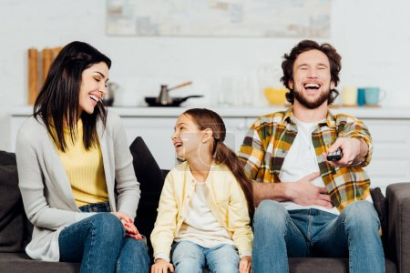 Photo for Happy father laughing while watching tv near attractive wife and kid - Royalty Free Image
