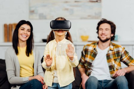 Photo for Selective focus of cute kid gesturing while wearing virtual reality headset near happy parents at home - Royalty Free Image