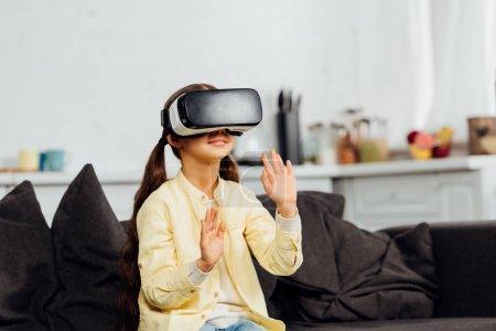 Photo pour Adorable enfant gestuelle tout en portant un casque de réalité virtuelle à la maison - image libre de droit
