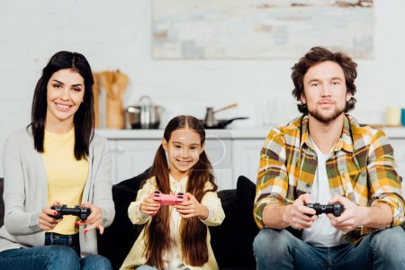 Photo for Cute and happy kid playing video game with parents at home - Royalty Free Image