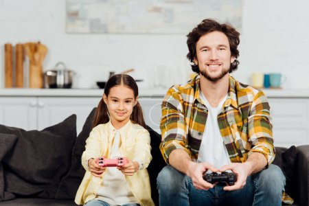 Photo for Happy child playing video game with bearded father at home - Royalty Free Image