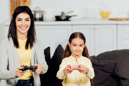 Photo for Happy kid playing with cheerful mother holding joystick at home - Royalty Free Image