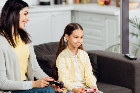 Photo for Happy kid playing video game with cheerful mother at home - Royalty Free Image