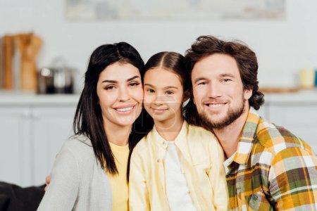 Foto de Familia positiva mirando a la cámara y sonriendo en casa - Imagen libre de derechos