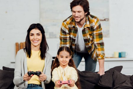 Photo for Happy man looking at cheerful wife and kid playing video game at home - Royalty Free Image