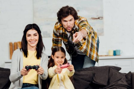 Photo for Handsome man pointing with finger near while cheerful wife and kid playing video game at home - Royalty Free Image