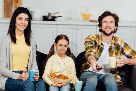 Photo pour Homme heureux retenant le contrôleur à distance et retenant la tasse près de la famille - image libre de droit