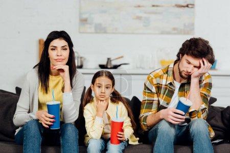 Photo pour Famille ennuyére retenant des tasses jetables tout en regardant le film à la maison - image libre de droit