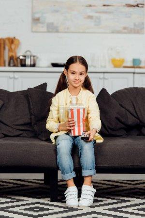 Photo pour Gosse heureux retenant le contrôleur à distance tout en s'asseyant sur le sofa avec le seau du maïs éclaté - image libre de droit