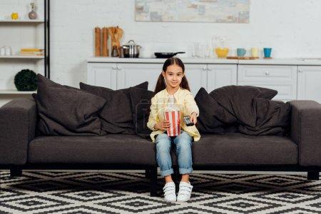 Photo pour Enfant mignon retenant le contrôleur à distance tout en s'asseyant sur le sofa avec le seau du maïs éclaté - image libre de droit
