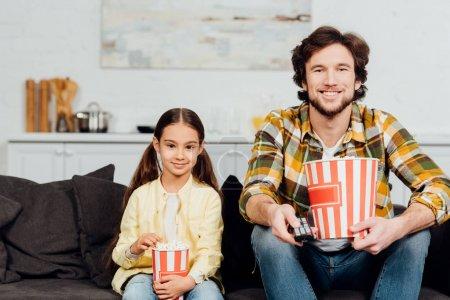 Photo pour Père et descendant heureux regardant la tv et retenant des seaux de maïs soufflé - image libre de droit