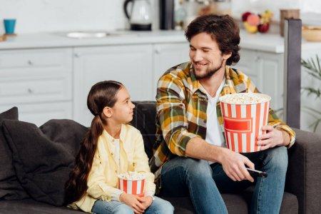 Photo pour Homme heureux regardant la fille mignonne tout en retenant le seau du maïs éclaté et du contrôleur à distance - image libre de droit