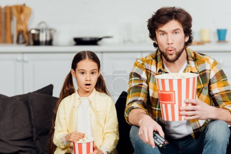 Photo for Surprised father and daughter watching movie and holding buckets of popcorn at home - Royalty Free Image