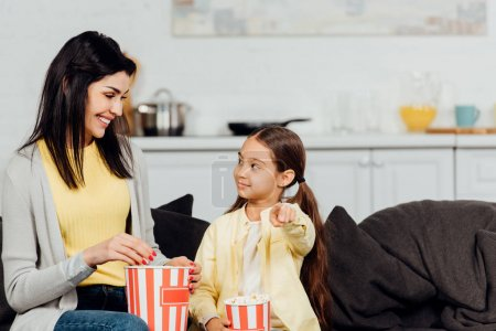 Photo for Happy kid pointing with finger and looking at mother holding bucket of popcorn - Royalty Free Image