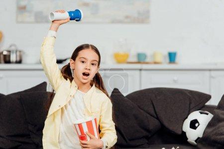 Foto de Lindo niño viendo el campeonato y sosteniendo cubo de palomitas de maíz mientras grita y gesturing en casa - Imagen libre de derechos