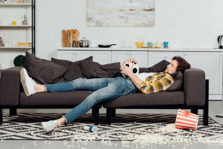 Photo for Tired man holding football and sleeping on sofa near bucket and popcorn on floor - Royalty Free Image