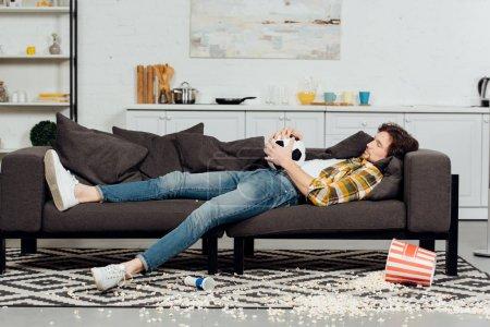 Photo pour Homme fatigué retenant le football et dormant sur le sofa près du seau et du maïs soufflé sur l'étage - image libre de droit