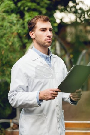 Photo for Serious scientist in white coat holding folder in green orangery - Royalty Free Image