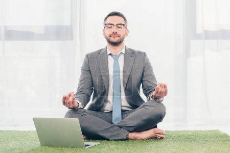 Photo pour Homme d'affaires s'asseyant sur le tapis d'herbe près de l'ordinateur portatif et méditant dans la pose de Lotus - image libre de droit