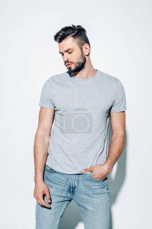Photo pour Bel homme barbu restant avec la main dans la poche sur le blanc - image libre de droit