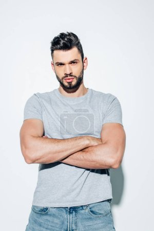 Photo for Handsome bearded man standing with crossed arms on white - Royalty Free Image