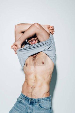 Foto de Hombre musculoso alegre quitándose la camiseta y sonriendo en blanco - Imagen libre de derechos