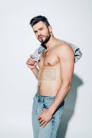 Photo pour Homme torse nu musculaire retenant le t-shirt tout en regardant l'appareil-photo sur le blanc - image libre de droit