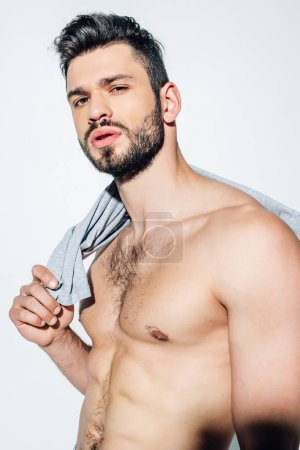 Photo for Shirtless bearded man holding t-shirt while looking at camera on white - Royalty Free Image