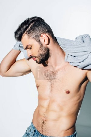 Photo for Shirtless bearded man holding t-shirt while standing on white - Royalty Free Image