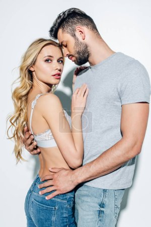 Photo for Attractive blonde woman looking at camera while standing with handsome man on white - Royalty Free Image