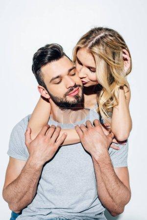 Photo pour Fille blonde attirante embrassant la joue de l'homme barbu beau dans le blanc - image libre de droit