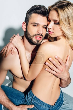 Photo for Handsome shirtless man looking at camera while touching naked blonde woman on white - Royalty Free Image