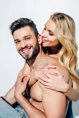 Photo for Happy woman hugging handsome boyfriend looking at camera on white - Royalty Free Image