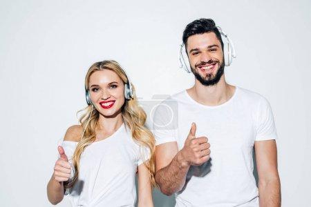 Foto de Hombre alegre y chica feliz mirando a la cámara mientras escucha música en auriculares y mostrando pulgares en blanco - Imagen libre de derechos