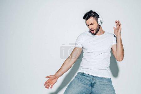 Photo pour Bel homme écoutant de la musique dans les écouteurs et chantant sur blanc - image libre de droit