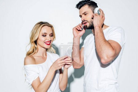 Photo for Happy blonde woman using smartphone near man in headphones on white - Royalty Free Image